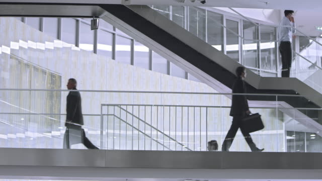 pan business people walking on the stairs in corporate building - staircase stock videos and b-roll footage