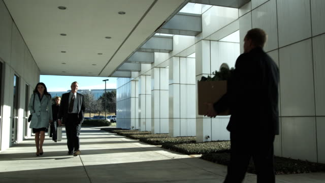 ws business people walking, one carrying box, dallas, texas, usa - unemployment stock videos and b-roll footage
