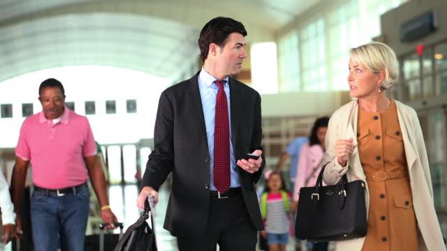 business people walking through airport terminal / text messaging - tjänstekvinna bildbanksvideor och videomaterial från bakom kulisserna