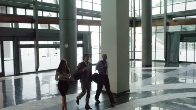 ws cs pan business people walking through office building's lobby / las vegas,nevada,usa - lobby stock videos & royalty-free footage