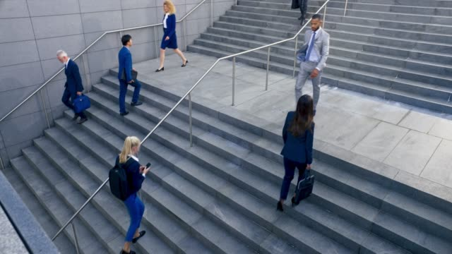 ld business people walking up and down the stairs outside a business building - moving down video stock e b–roll