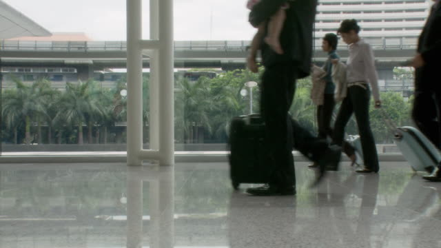 ms pan business people walking with travel luggage in lobby / bangkok, thailand - schuhwerk stock-videos und b-roll-filmmaterial