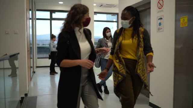 vídeos y material grabado en eventos de stock de personas de negocios con máscaras faciales protectoras que tienen una discusión en el edificio de oficinas - piso de edificio