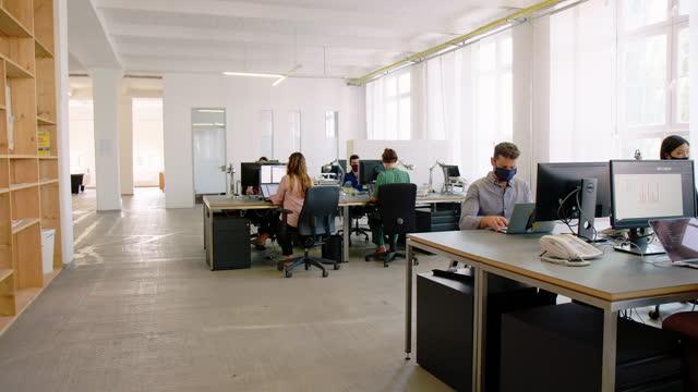 vídeos de stock, filmes e b-roll de empresários com máscaras faciais protetoras trabalhando no escritório - alcançar