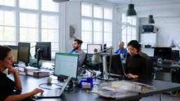 Business people working in a busy open plan office