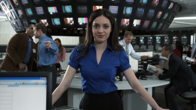 T/L Business people working in control room, focus on woman in front of camera, Dallas, Texas, USA
