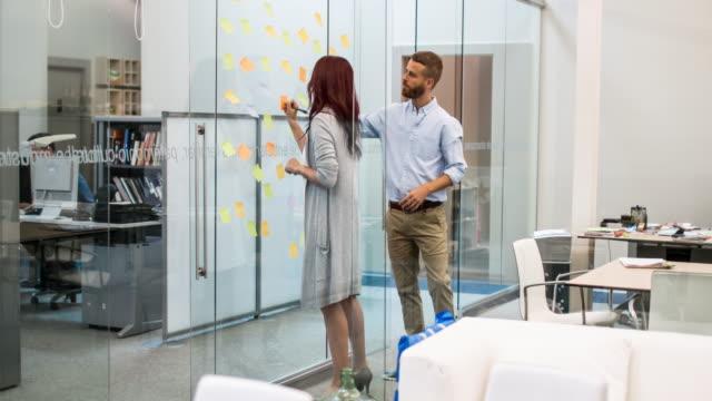 Affärsmän skriver idéer på självhäftande anteckningar i konferensrum