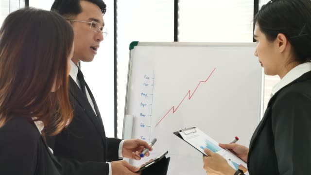 business person discuss charts drawn on whiteboard. man shows details on the screen woman listens holding clipboard in her hands.their office is developer and modern looking. - sales pitch stock videos & royalty-free footage