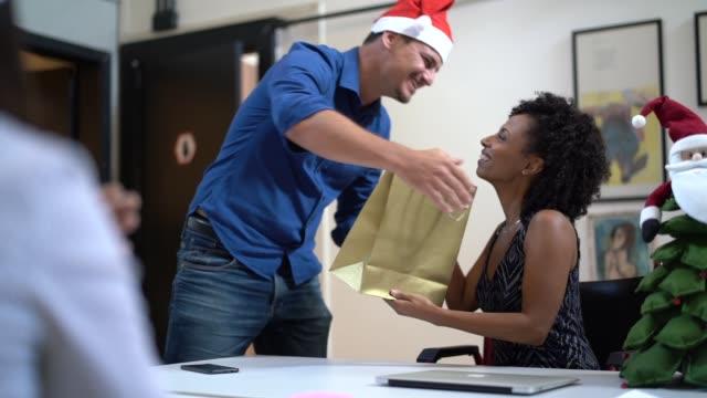 business person giving christmas presents at work / amigo secreto - pardo brazilian stock videos & royalty-free footage
