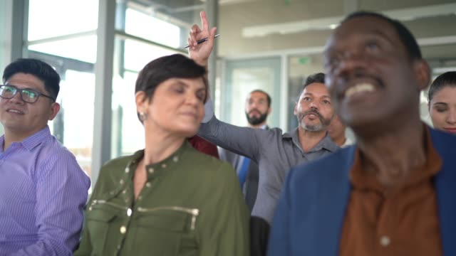 vídeos de stock, filmes e b-roll de empresário levantando a mão para questionar de palestrante em seminário - concentração