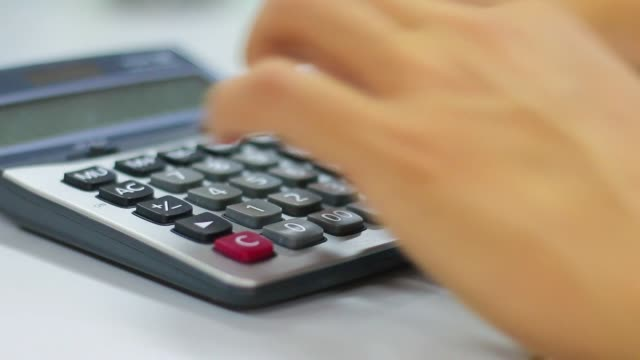 Business person uses calculator analysis financial data