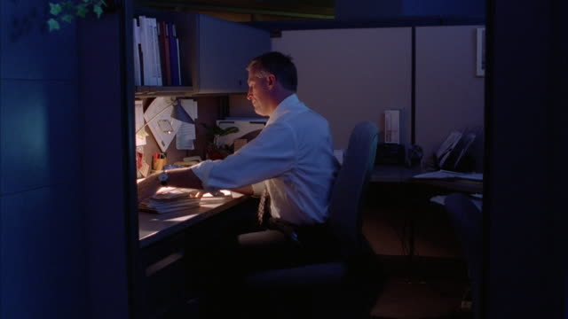 A business professional turns of his lamp and rests his head on his desk