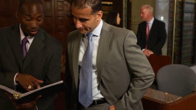 stockvideo's en b-roll-footage met business professionals discuss documents - wet