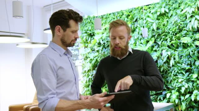 business-profis diskutieren projektdetails auf digitalen tablets - tablet benutzen stock-videos und b-roll-filmmaterial