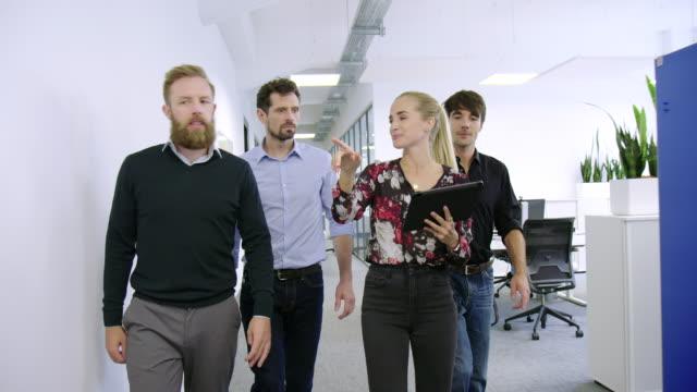 vídeos y material grabado en eventos de stock de profesionales de negocios caminando juntos en el nuevo corredor de oficinas - new