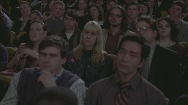 Business professionals watch a presentation in a crowded auditorium.
