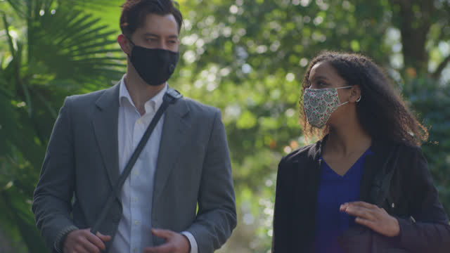 business professionals wearing face masks casually chat has they walk down a sidewalk - walkable city stock videos & royalty-free footage