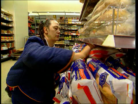 Sainsbury's New Jobs ITN Woman worker working at chiller cabinet in Sainsbury's store Woman along pushing trolley Woman placing bread on shelf...