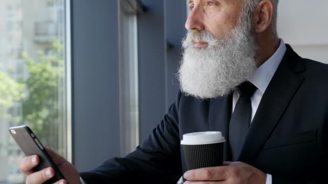 verksamhet. senior affärsman läser ett meddelande på en smartphone - 50 59 years bildbanksvideor och videomaterial från bakom kulisserna