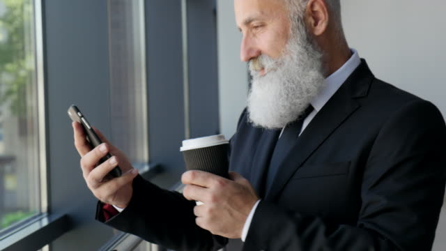 business. senior businessman reading a message on a smartphone - 50 59 years video stock e b–roll