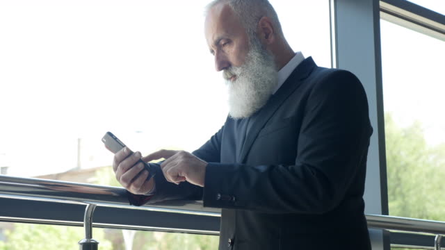 business. senior businessman reading a message on a smartphone - big hair stock videos and b-roll footage