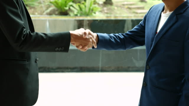 Business shaking hands for accept agreement in Office interior