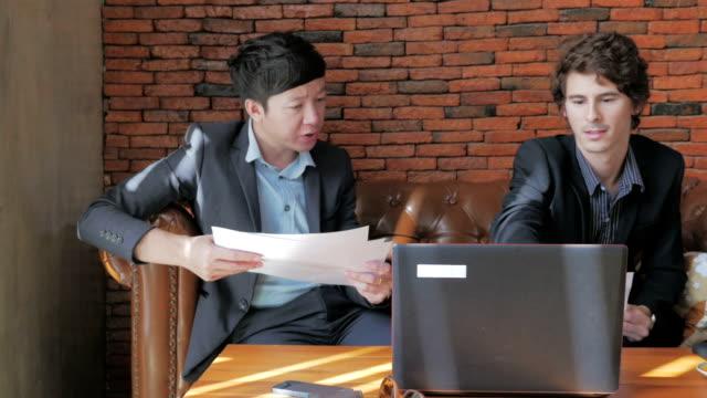 Business Talk der asiatischen und amerikanischen Geschäftsleute und Kamerafahrt mit Dolly