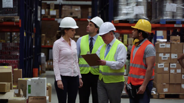 business team and warehouse supervisor walking with their boss at the warehouse while he looks at clipboard and points at different shelves - world trade organisation stock videos & royalty-free footage