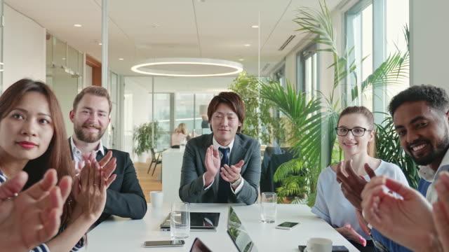 vídeos y material grabado en eventos de stock de equipo de negocios celebrando una presentación fuerte con aplausos mirando a la cámara - mesa negociadora
