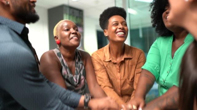 vidéos et rushes de équipe d'affaires encourageant joignant des mains dans le huddle - serré