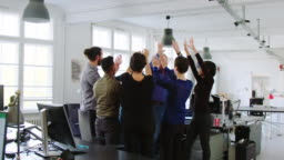 Business team cheering joining hands in huddle