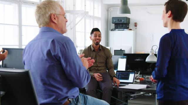 vídeos y material grabado en eventos de stock de equipo de negocios aplaudiendo a un compañero de trabajo en la reunión de personal - solución