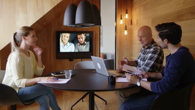 vídeos y material grabado en eventos de stock de equipo de negocios discutiendo durante videoconferencia - conferencia telefonica