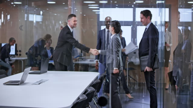 ds business team entering the glass conference room and greeting the other team - businesswear stock videos & royalty-free footage
