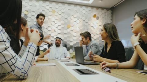 vídeos de stock, filmes e b-roll de equipe do negócio que tem uma reunião de negócio com homem de negócios árabe no escritório - presidente de empresa