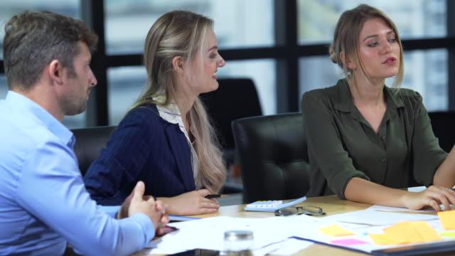 vidéos et rushes de équipe d'affaires ayant une réunion de discussion dans la salle - étude de marché