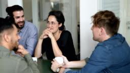 Business team having fun conversation during coffee break at office