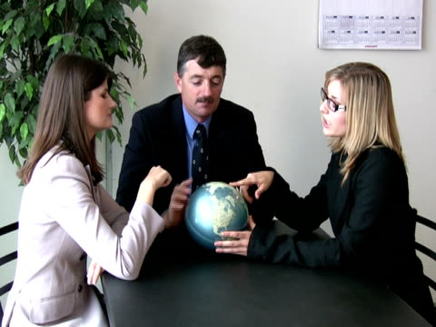business team holds out globe to camera - mid length hair stock videos & royalty-free footage