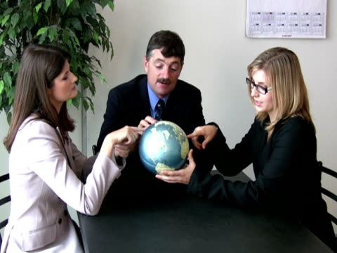 business team holds up globe - mid length hair stock videos & royalty-free footage