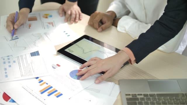 ビジネス チームは、自分の会社の金融開発についてアイデアを共有します。彼らは財務データやグラフを議論しています。 - paperwork点の映像素材/bロール