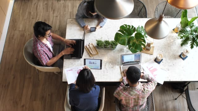 business team sitting at the table at loft office and working - table top view stock videos & royalty-free footage