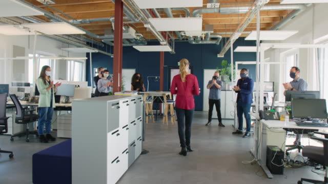 vidéos et rushes de réunion debout d'équipe d'affaires avec la distance sociale - nouvelle entreprise