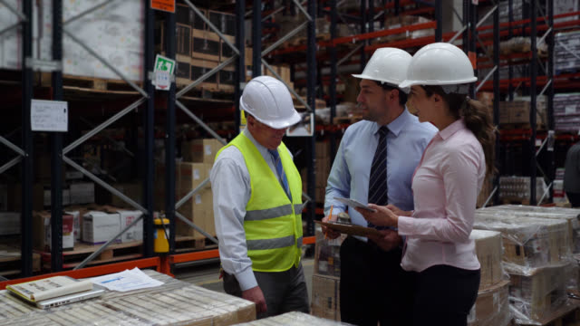 business team supervising operations of a distribution warehouse talking and looking at documents on clipboard - world trade organisation stock videos & royalty-free footage