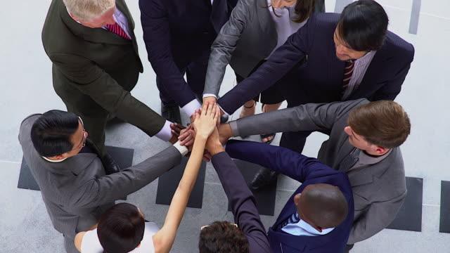 vídeos de stock, filmes e b-roll de os grupos dos trabalhos de equipa do negócio de povos multi-ethnic empilharam a aproximação, conceito da unidade. disparado da vista superior. - unidade