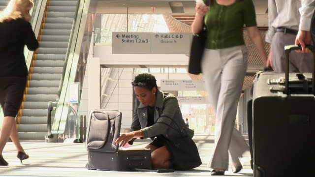 vídeos de stock, filmes e b-roll de business traveler searching through clothes on airport floor - desempacotando