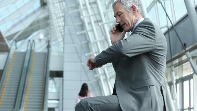 business traveler talking on mobile phone in airport terminal - ロビー点の映像素材/bロール