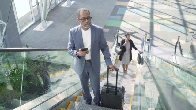 business traveler text messaging on escalator in airport - business travel stock videos & royalty-free footage