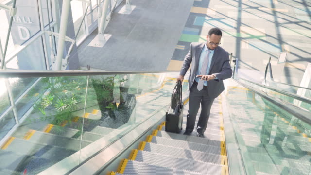 Business traveler text messaging on escalator in airport