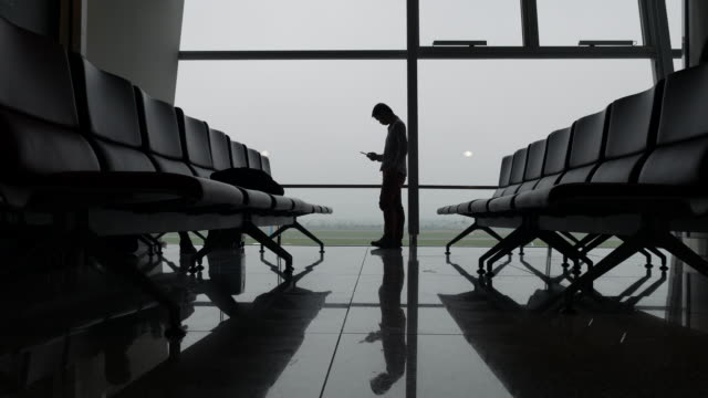 business travelers silhouettes at airport terminal - business travel stock videos & royalty-free footage
