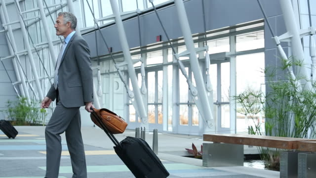 WS PAN Business Travelers Walking Through Airport Lobby with Luggage / Virginia Beach, Virginia, United States